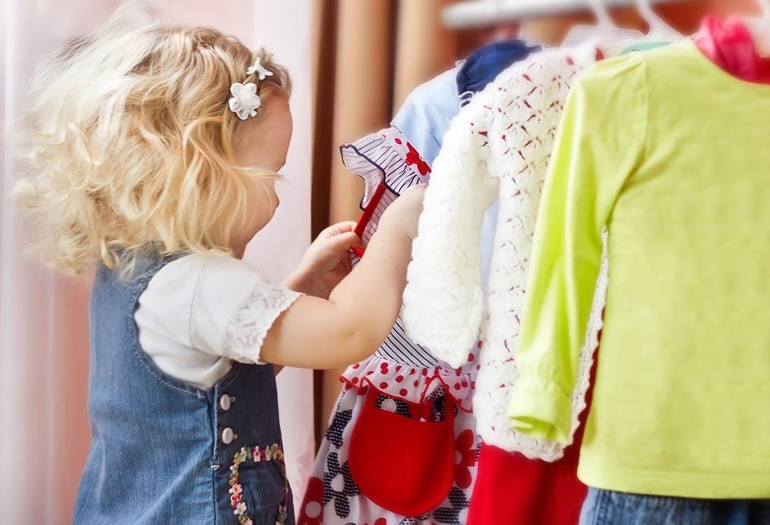 девочка выбирает одежду